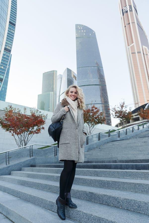 Oavkortad tillväxt för stående av det blonda kvinnaanseendet på stege royaltyfri bild