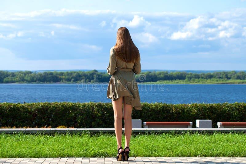Oavkortad tillväxt för tillbaka siktsstående, ung härlig brunettkvinna i en grön klänning arkivbild