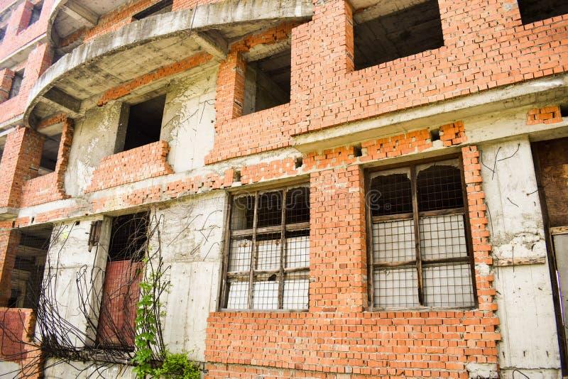 Oavslutad byggnad i centret ?vergett byggnadsprojekt med r?da tegelstenar och l?s vegetation arkivfoton