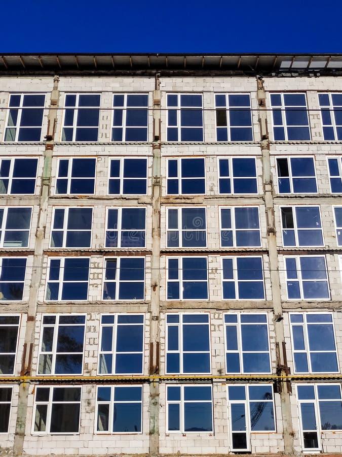 Oavslutad byggnad med nya fönster och betongväggar, innan fullföljande och att måla arkivbild