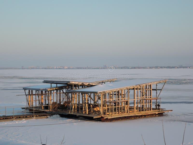 Oavslutad struktur på den djupfrysta floden på bakgrunden av vinterstaden på solnedgången royaltyfri foto
