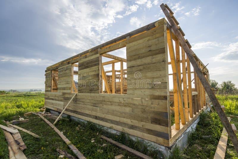 Oavslutat ekologiskt hus under konstruktion i grönt fält på bakgrund för blå himmel Diken som fylls med cement och träväggar arkivbild