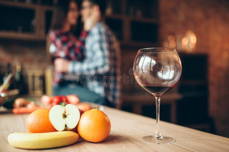 Oavslutat exponeringsglas av vin, frukter, kopplar ihop att kyssa royaltyfri fotografi
