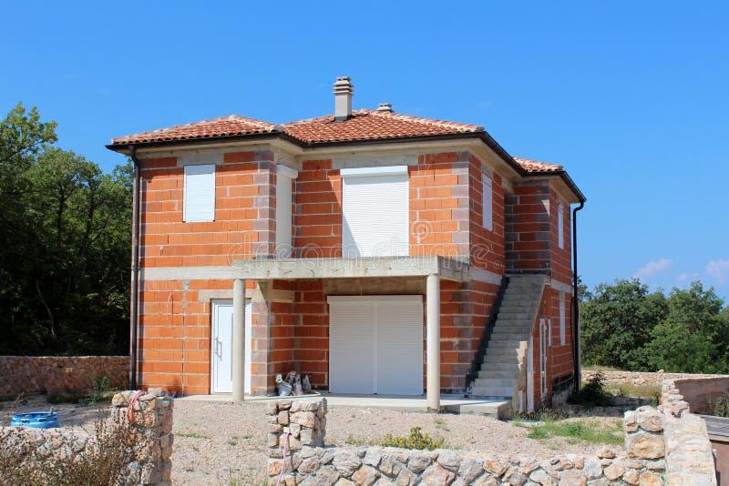 Oavslutat familjhus för röda tegelstenar med nya dörrar och fönster som omges med stenväggen och byggnadsmaterial med träd och arkivfoto
