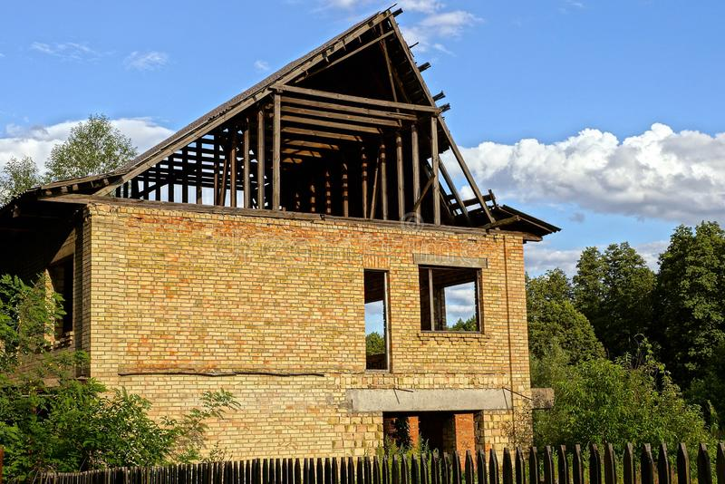 Oavslutat hus av brun tegelsten och trätaket bland de gröna träden bak staketet arkivbild