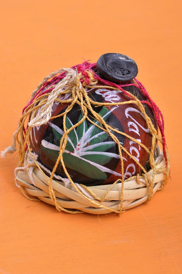 Oaxaca clay mezcal container. Typical Mexican handicraft mezcal container made of black clay from Oaxaca, Mexico on orange table royalty free stock images
