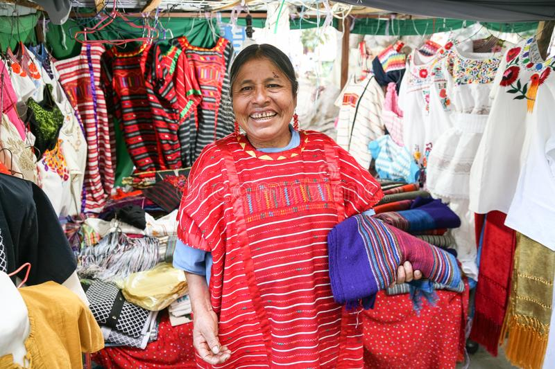 Mexican woman selling traditional mexican shawl and clothes in royalty free stock photo