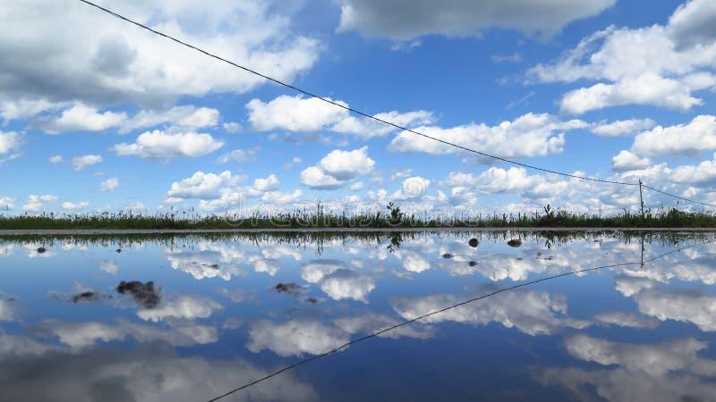 Obłoczna niebo odruchu błękitne wody obrazy stock