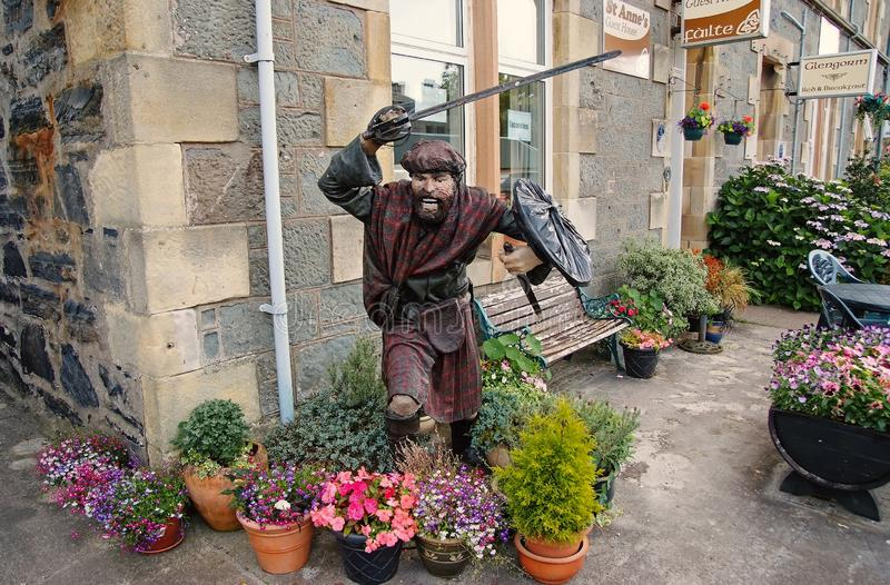 Oban, United Kingdom - February 20, 2010: warrior statue on building corner with pot plants. Town house with bench and. Flowers in yard. Victorian style stock image
