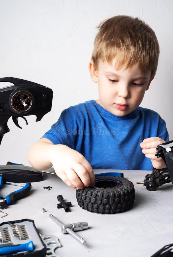Obby radia wzorowanie: troszkę chłopiec naprawia kontrolującego samochodowego powozika z śrubokrętem w błękitnej koszulce obraz stock
