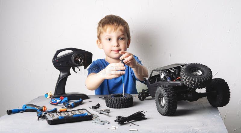 Obby radia wzorowanie: troszkę chłopiec naprawia kontrolującego samochodowego powozika z śrubokrętem w błękitnej koszulce zdjęcie royalty free