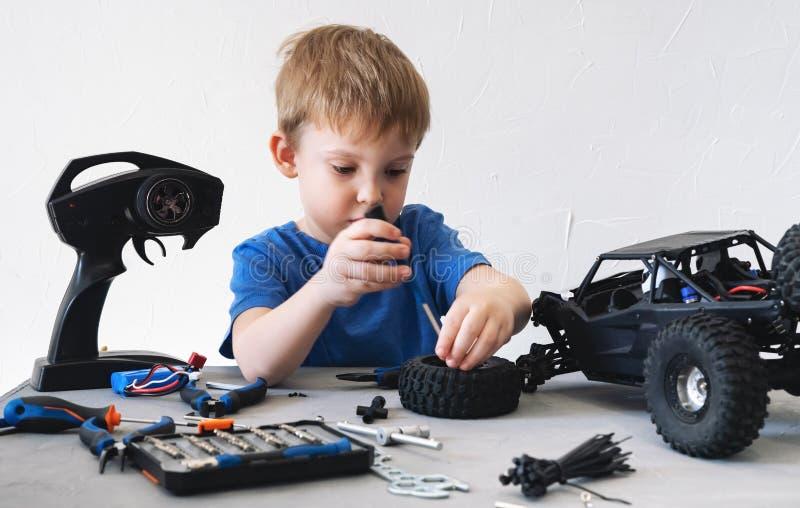 Obby radia wzorowanie: troszkę chłopiec naprawia kontrolującego samochodowego powozika z śrubokrętem w błękitnej koszulce obrazy royalty free