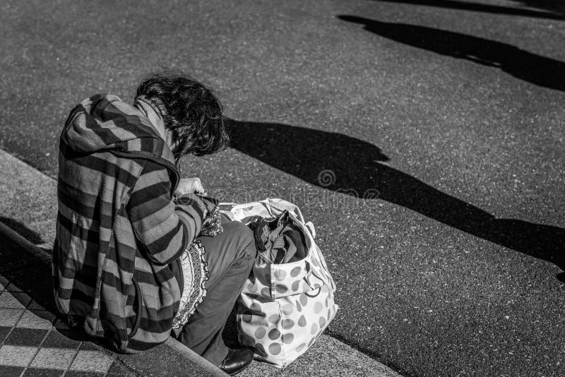 Obdachlose Dame, die außerhalb der Bahnstation sitzt stockfoto