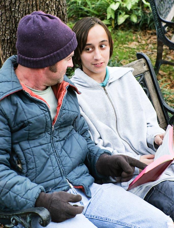 Obdachlose Familie mit Bibel stockbild