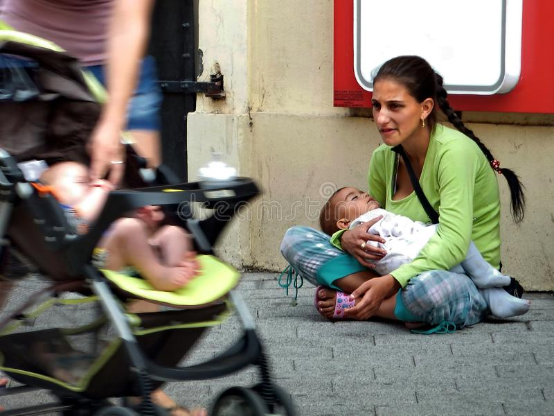 Obdachlose Frau, die auf der Pflasterung mit Baby in ihren Händen sitzt stockfotografie