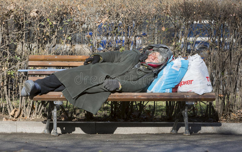 Obdachlose Frau, die auf einer Bank schläft stockfotos