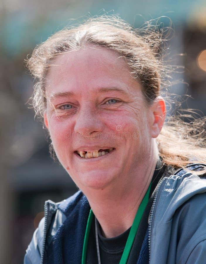 Obdachlose Frau, die mit den schlechten Zähnen lächelt lizenzfreies stockbild