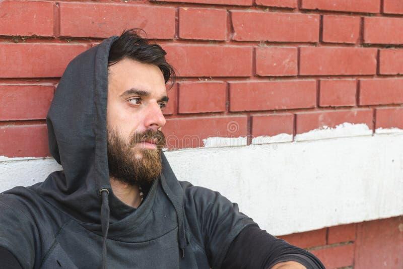 Obdachlose Manndroge und Alkohols?chtiger allein sitzend und deprimiert auf der Stra?e, die an einer Geb?udewand des roten Backst lizenzfreies stockfoto