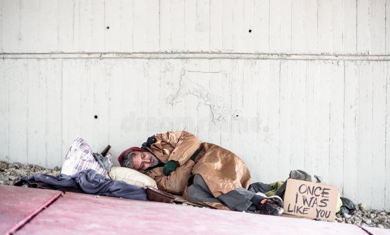 Obdachloser Bettlermann, der auf dem Grundfreien in der Stadt, schlafend liegt Kopieren Sie Platz stockbild