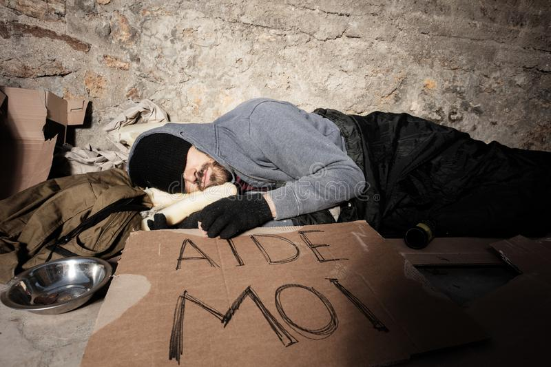 Obdachloser Mann in der alten Kleidung schlafend auf der Straße stockbild
