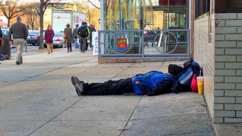 Obdachloser Mann, der auf Bürgersteig schläft lizenzfreie stockfotografie
