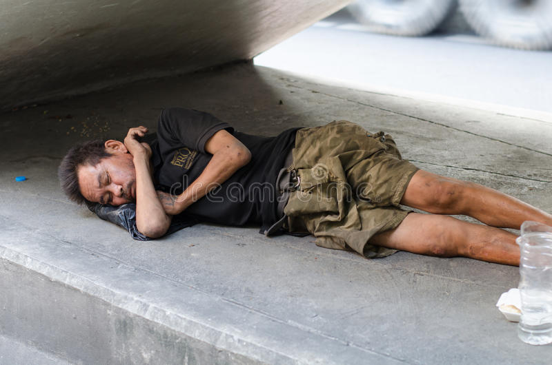Obdachloser Mann, der auf dem Bürgersteig schläft stockfoto