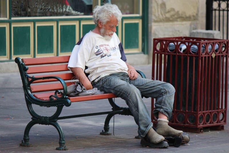 Obdachloser Mann, der auf einer Park-Bank auf Stephen Avenue in Calgary Alberta sitzt lizenzfreies stockbild