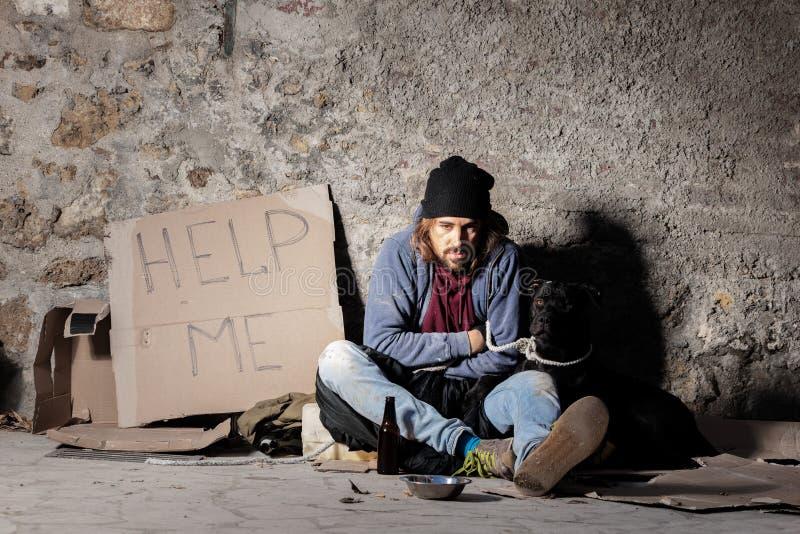 Obdachloser Mann, der auf der Straße mit einem Hund sitzt stockfotografie