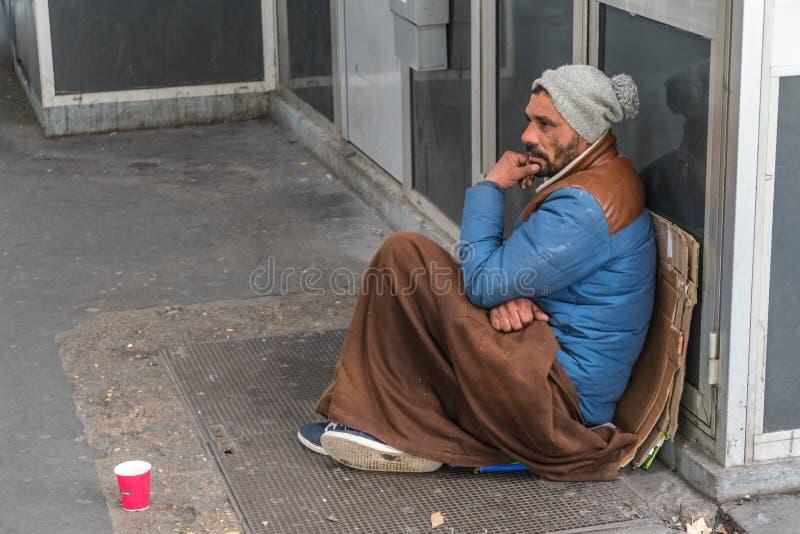 Obdachloser Mann, der auf der Straße sitzt stockfotografie