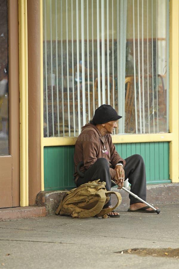 Obdachloser Mann, der auf Straße sitzt stockfotografie