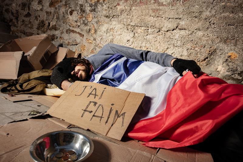 Obdachloser Mann, der draußen unter französischer Flagge schläft lizenzfreies stockfoto