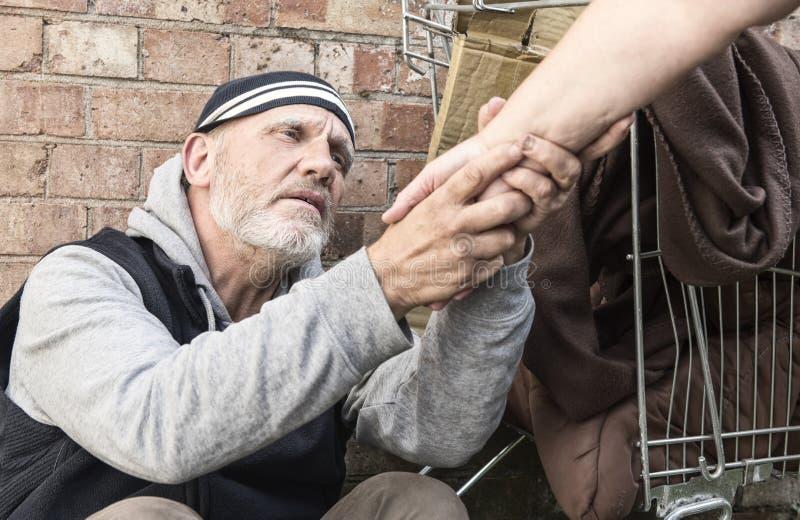 Obdachloser Mann, der ein woman& x27 nimmt; s-Hand stockfoto