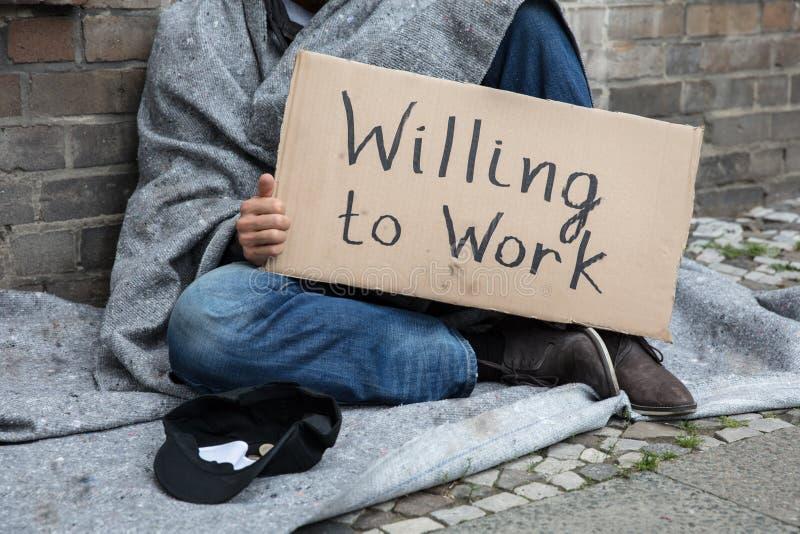 Obdachloser Mann, der Pappe mit dem Text gewillt ist zu arbeiten hält lizenzfreie stockfotos