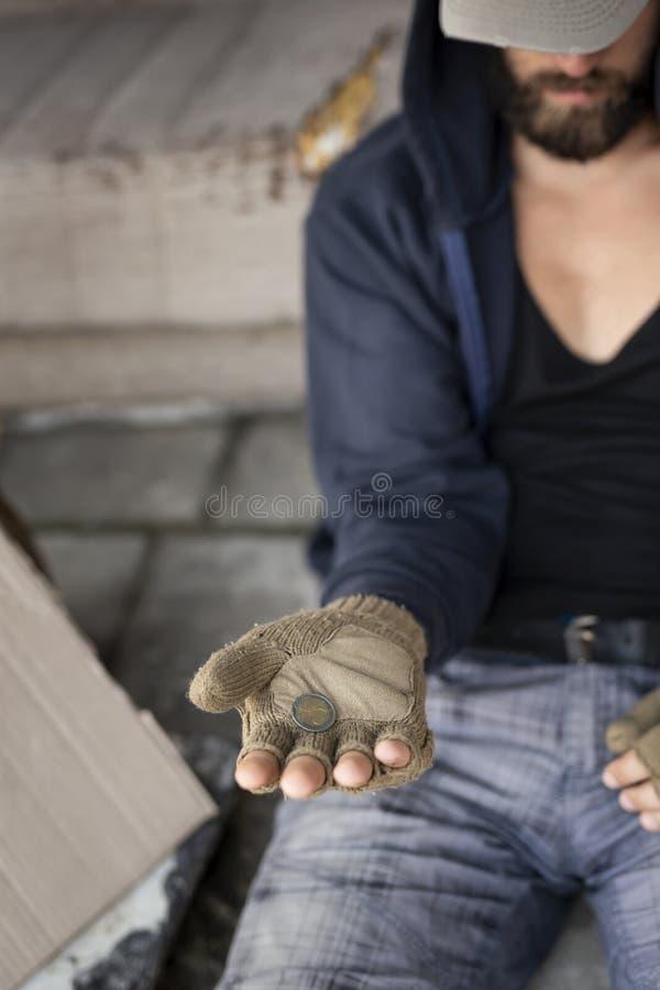 Obdachloser Mann, der um Geld bittet stockfotografie