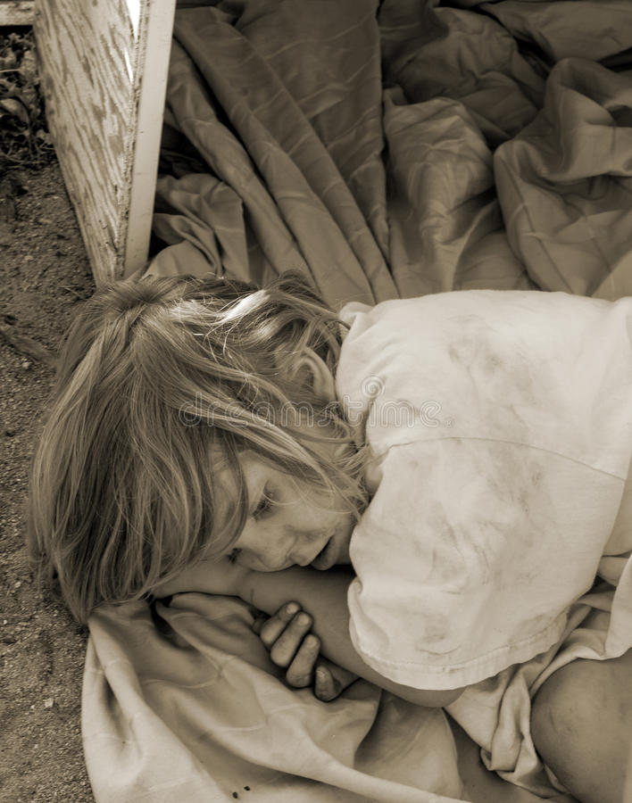Obdachloses Kind, das in einem alten Kasten niederlegt lizenzfreie stockfotos