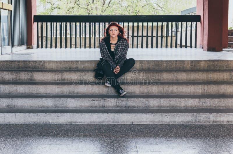 Obdachloses Mädchen, junges rotes Haarmädchen, das allein draußen auf der Treppe des Gebäudes mit dem Hut- und Hemdgefühl besorgt stockfoto