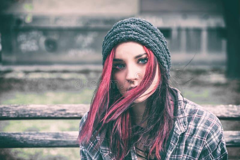 Obdachloses Mädchen, junges rotes Haarmädchen, das allein draußen mit Hut sitzen und Hemd besorgt und deprimiert, nachdem sie ein lizenzfreie stockfotografie