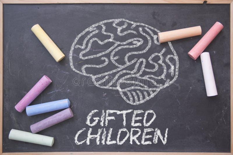 Obdarzeni dzieci i edukacji pojęcie pisać na blackboard w sali lekcyjnej Móżdżkowy rysunek i niektóre barwiona kreda na chalkboar obraz royalty free