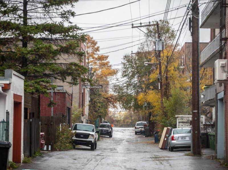 Obdrapana typowa północnoamerykańska mieszkaniowa ulica w jesieni w Montreal, Quebec, podczas deszczowego dnia z samochodami park obraz royalty free