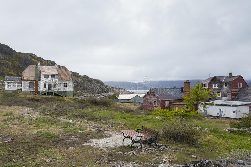 Obdrapani drewniani domy z obieraniem malują w Greenland dalekiego ducha górniczej wiosce zdjęcie stock