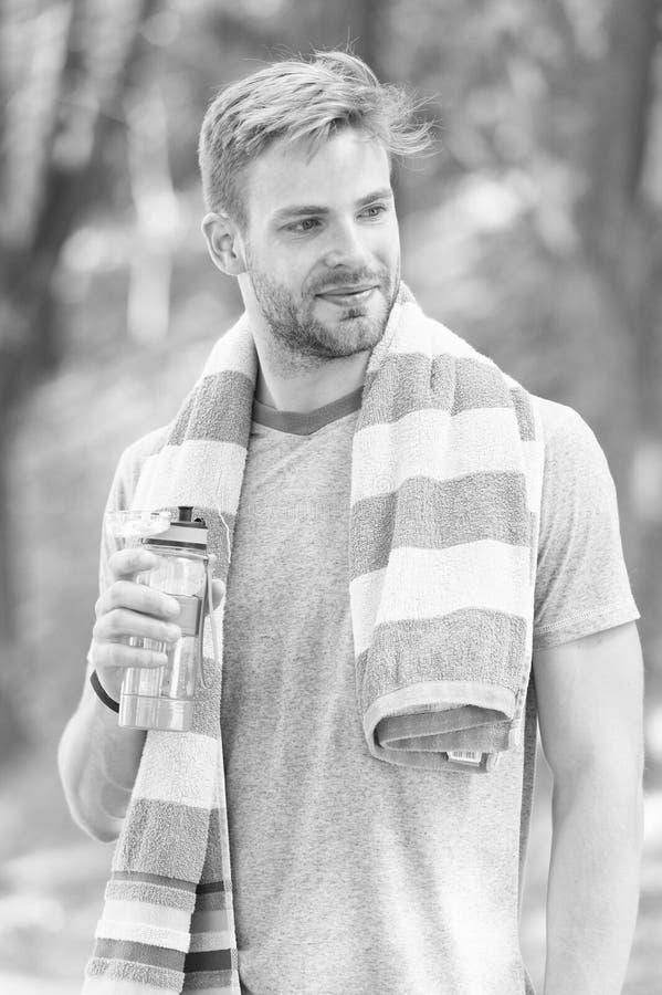 Obedece tu sed Deportista sediento Hombre con barba sostiene una botella de agua potable para calmar su sed Sed sofocante foto de archivo libre de regalías