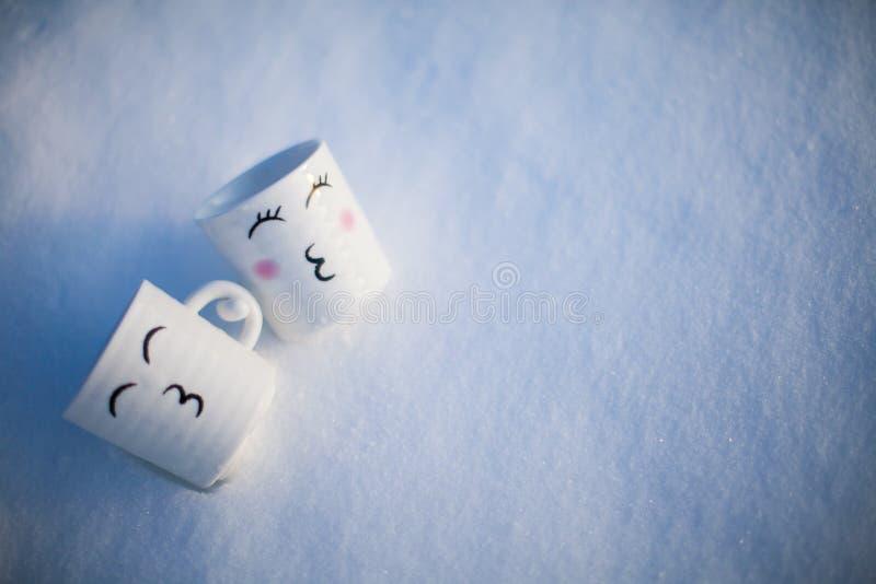 Obejmować dwa kubka z obrazkiem w śniegu fotografia stock