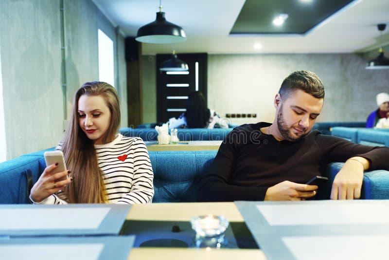 Obejmować pary używa telefon komórkowego w kawiarni stonowany Selekcyjna ostrość zdjęcia royalty free