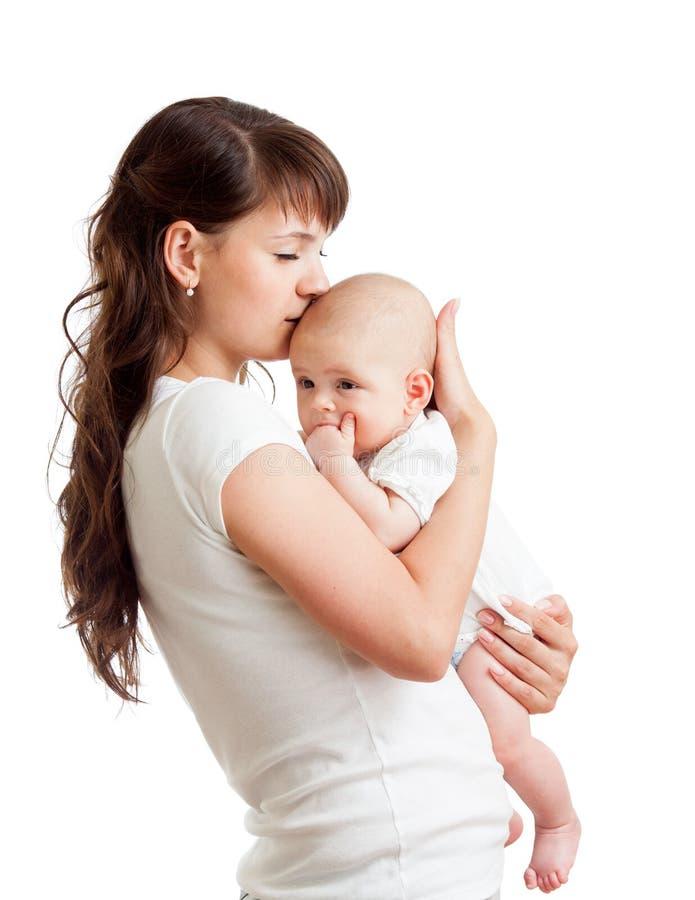 Obejmowania kochający macierzysty całowanie odizolowywający jej dziecko zdjęcia stock