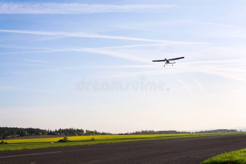 Obemannat flyg- medelbevakningsurr med ljus- och kameralandning på flygplatslandningsbanan, jordning, flygfält, solig morgon royaltyfri foto