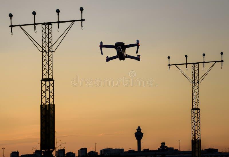 Obemannat surrflyg nära landningsbana på flygplatsen i - mellan att att närma sig landningsbanabelysning på solnedgången royaltyfri bild