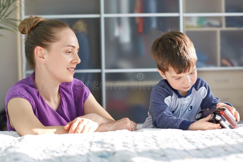 Oben holen und Kinder Konzept Horizontaler Schuss der recht jungen Mutter im purpurroten zufälligen T-Shirt, kümmert sich um ihre stockbild