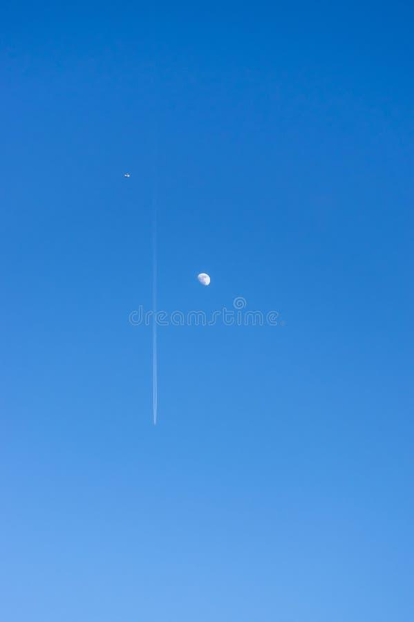 Oben schauen in den hellen blauen und wolkenlosen Himmel mit Mond und einem Passagierflugzeug mit Contrails und einem kleinen Flu stockfotografie