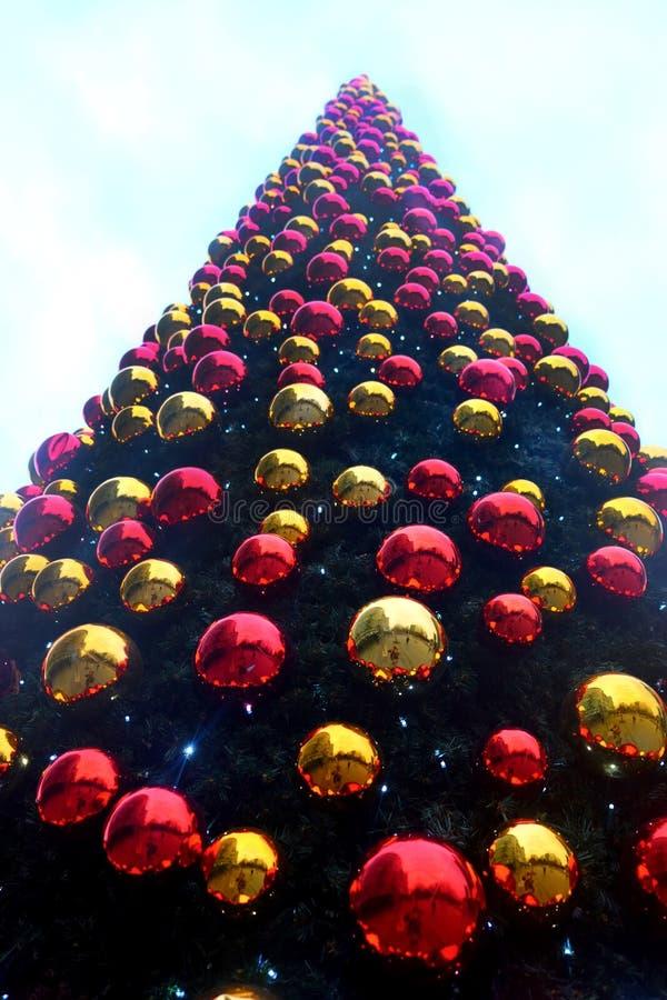 Oben schauen zur Spitze eines sehr großen Weihnachtsbaums bedeckt in den Hunderten vom Rot und vom Goldweihnachtsflitter stockfotografie