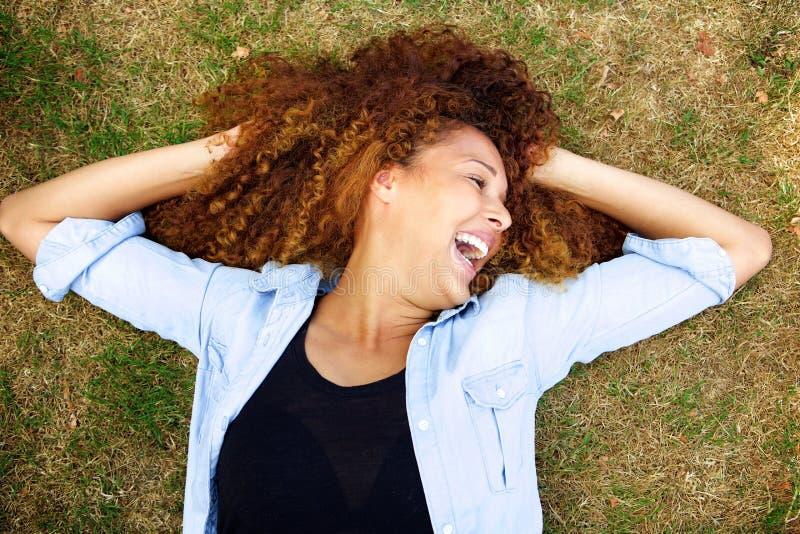 Oben von der jungen Frau, die auf Gras lacht stockbild